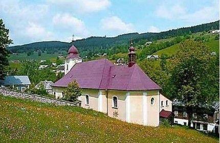 Kostel Nejsvětější Trojice ve Velké Úpě / Pohled od lesa, na snímku je vidět část zdi hřbitova, který ke kostelu přiléhá. Hřbitov byl v roce 2019 zregenerován na náklady města Pec pod Sněžkou.